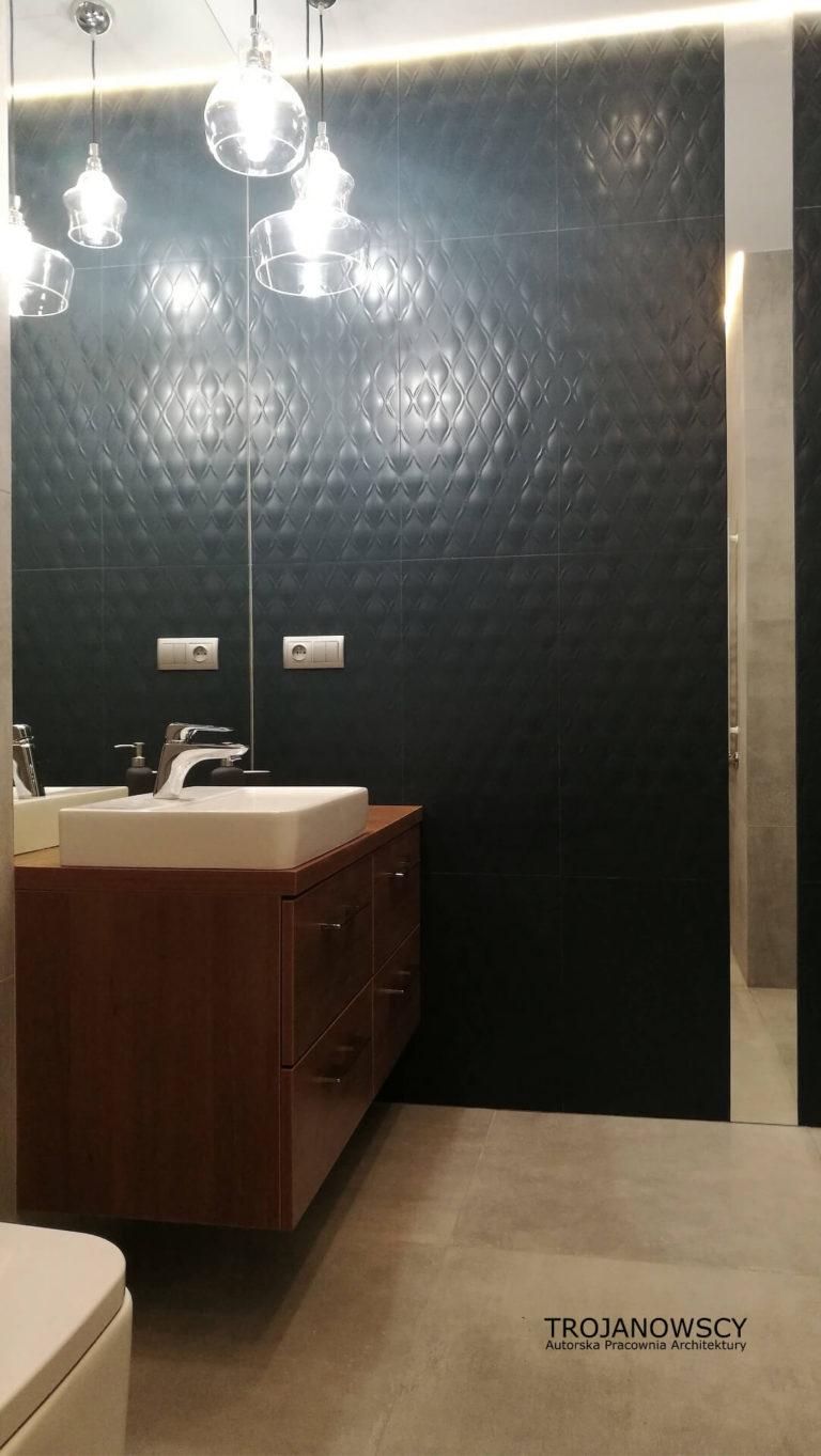 minimalistyczna łazienka, designerska ciemna ściana, drewniana komoda